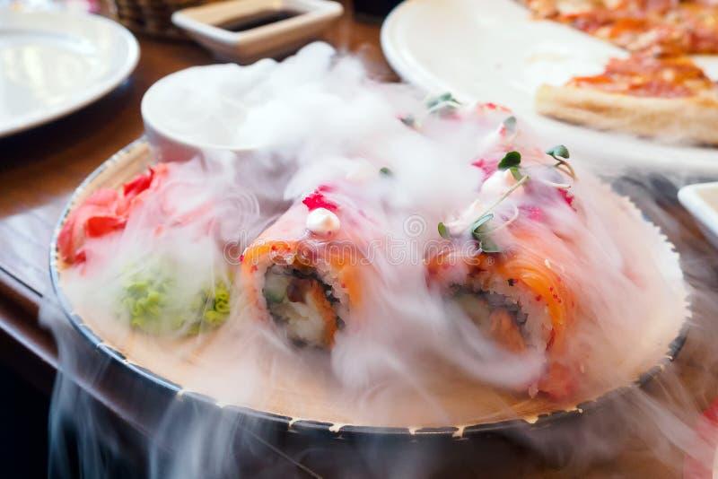 Rotoli di sushi di color salmone con il fumo del ghiaccio secco, alimento giapponese fotografie stock