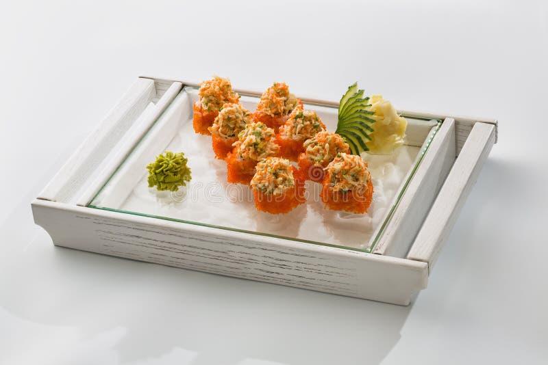 Rotoli di sushi con il caviale di color salmone e rosso su un piatto isolato su wh immagini stock