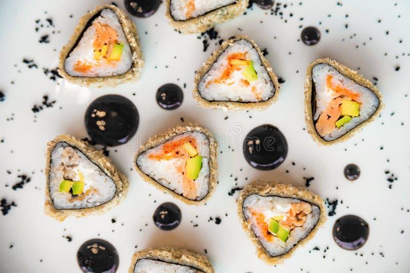 Rotoli di sushi deliziosi del triangolo di vista superiore sul piatto fotografia stock libera da diritti