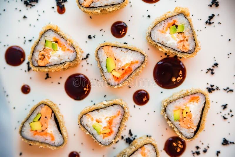 Rotoli di sushi deliziosi del triangolo di vista superiore sul piatto fotografia stock