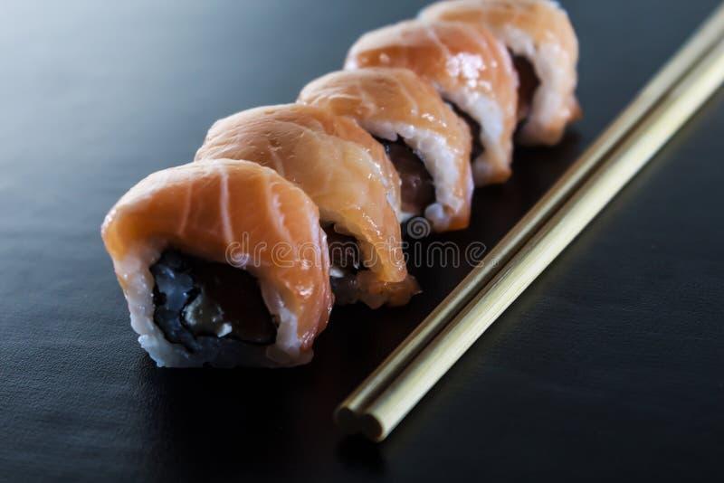 Rotoli di sushi freschi deliziosi con formaggio di color salmone e cremoso sulla banda nera Alimento giapponese tradizionale, con fotografia stock libera da diritti