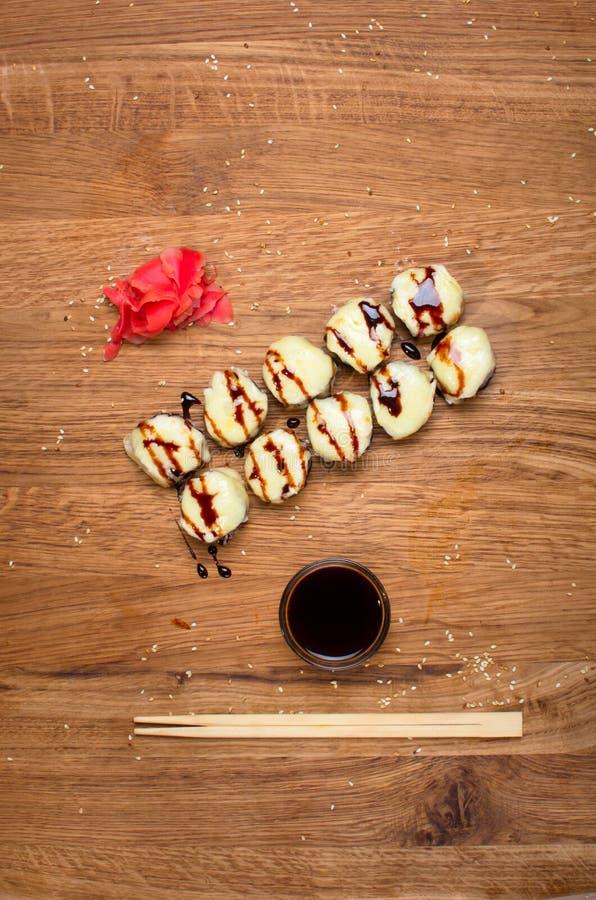 Rotoli di sushi insoliti su una tavola di legno Rotoli di sushi ucraini con formaggio al forno ed i granchi immagini stock