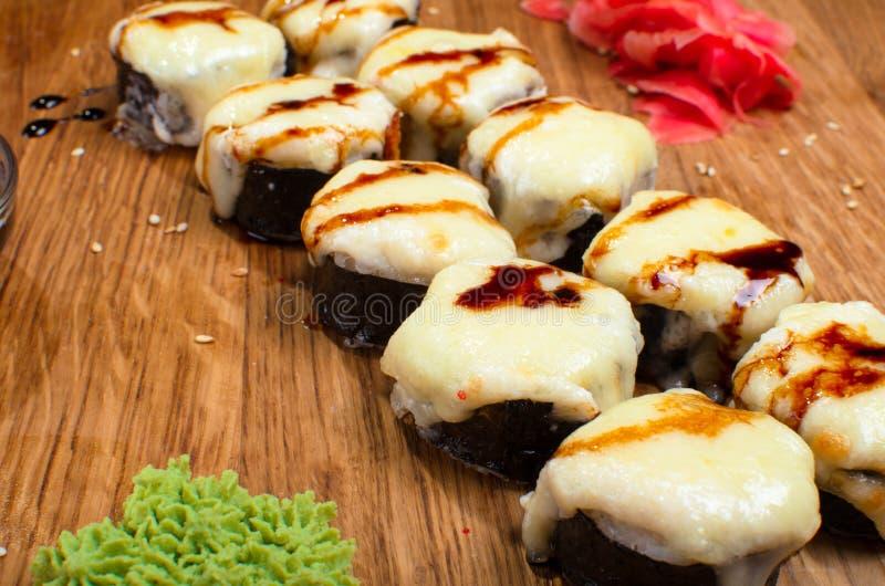 Rotoli di sushi insoliti su una tavola di legno Rotoli di sushi ucraini con formaggio al forno ed i granchi fotografie stock libere da diritti