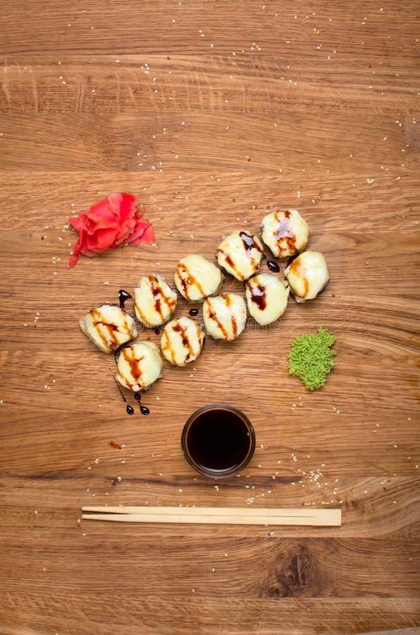 Rotoli di sushi insoliti su una tavola di legno Rotoli di sushi ucraini con formaggio al forno ed i granchi fotografia stock