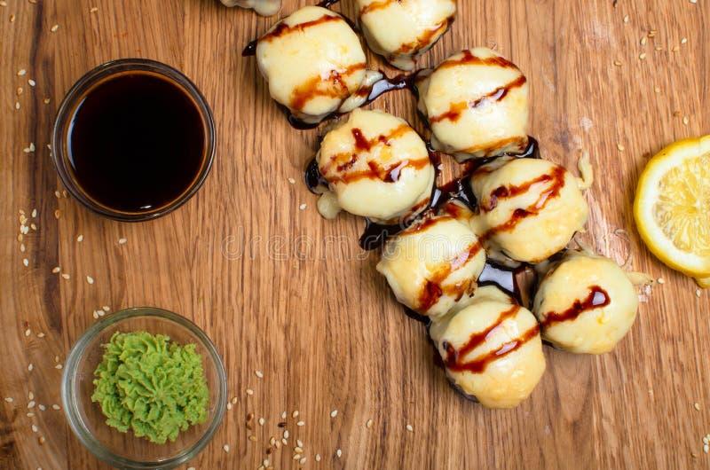 Rotoli di sushi insoliti su una tavola di legno Rotoli di sushi ucraini con formaggio al forno ed i granchi immagine stock