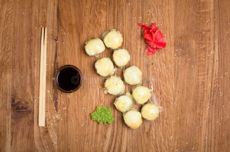 Rotoli di sushi insoliti su una tavola di legno Rotoli di sushi ucraini con formaggio al forno ed i granchi fotografie stock