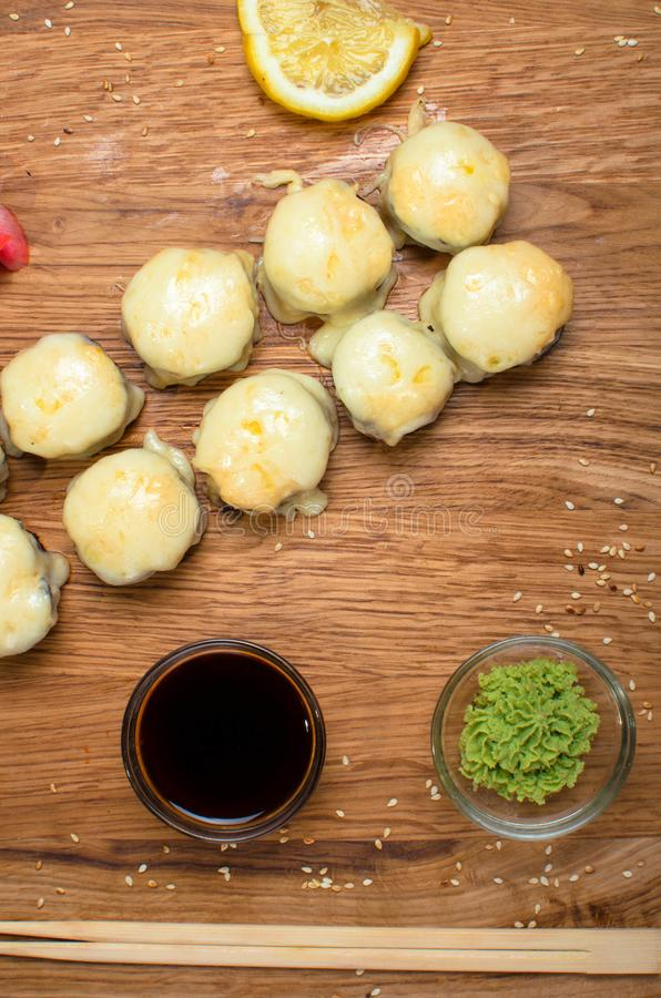 Rotoli di sushi insoliti su una tavola di legno Rotoli di sushi ucraini con formaggio al forno ed i granchi fotografia stock libera da diritti