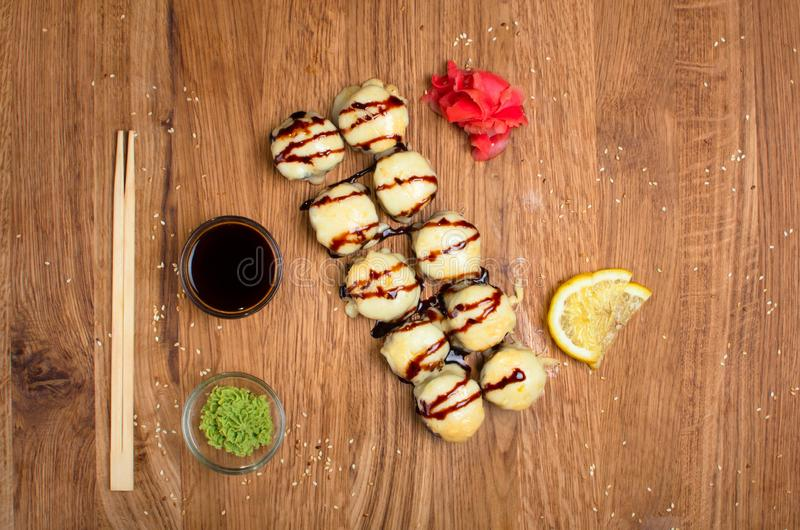 Rotoli di sushi insoliti su una tavola di legno Rotoli di sushi ucraini con formaggio al forno ed i granchi immagine stock libera da diritti