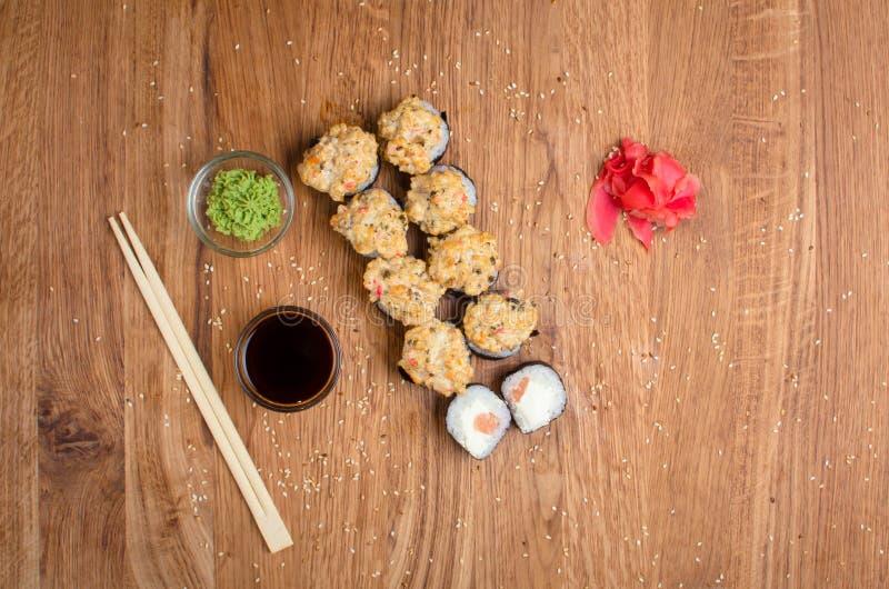 Rotoli di sushi insoliti su una tavola di legno Rotoli di sushi ucraini con formaggio al forno ed i granchi immagini stock libere da diritti
