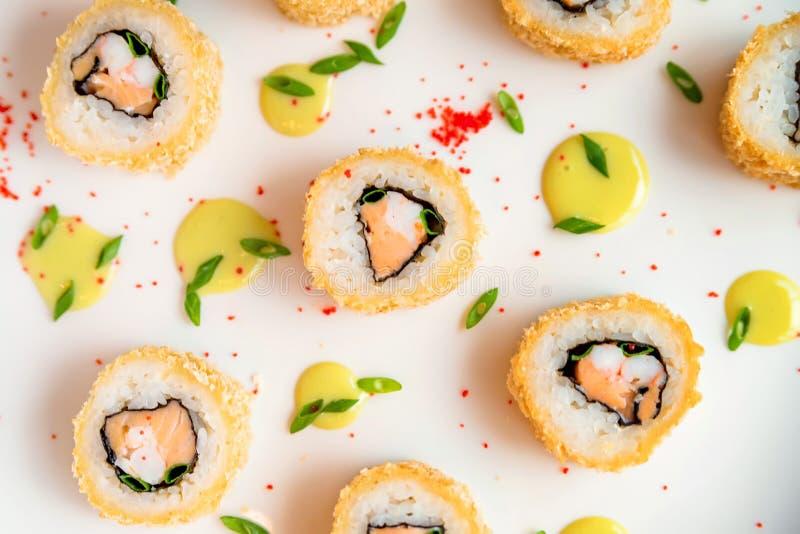 Rotoli di sushi sparsi sulla fine bianca del fondo su immagini stock libere da diritti