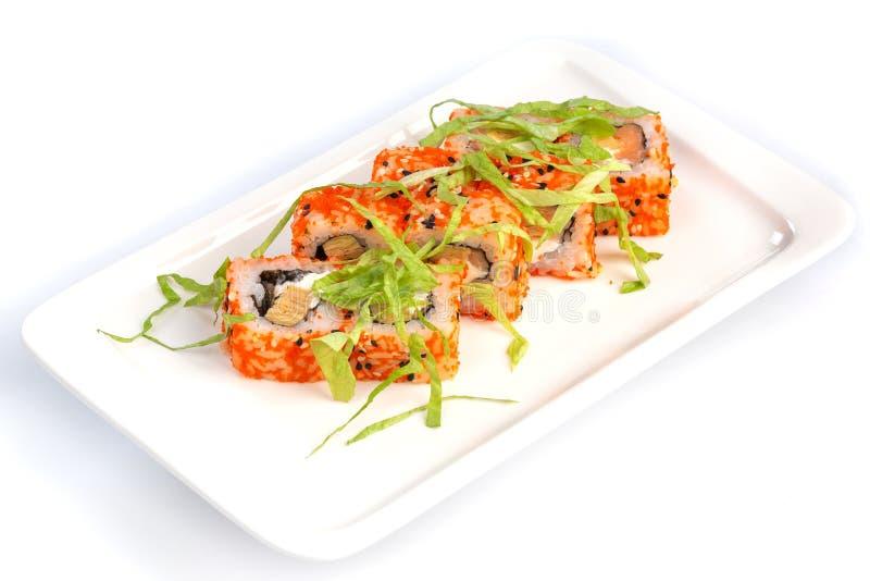 Rotoli di sushi stabiliti su un piatto bianco su un fondo bianco isolato immagini stock