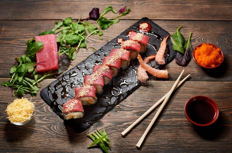Rotoli giapponesi che serviscono con il tonno, semi di sesamo, gamberetto, insalata della miscela, formaggio grattugiato, caviale fotografie stock