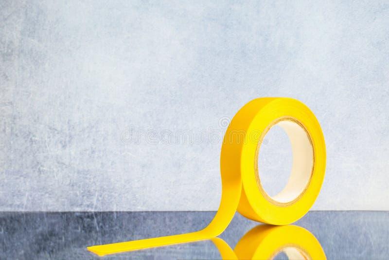 Rotoli il nastro elettrico giallo su un fondo grigio fotografie stock libere da diritti