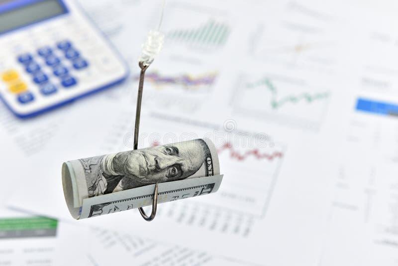 Rotolo acciambellato della banconota in dollari degli Stati Uniti 100 su un gancio di pesca fotografie stock libere da diritti