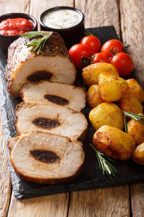 Rotolo al forno della carne di maiale farcito con le prugne servite con il verticale del primo piano delle salse e delle patate n immagine stock