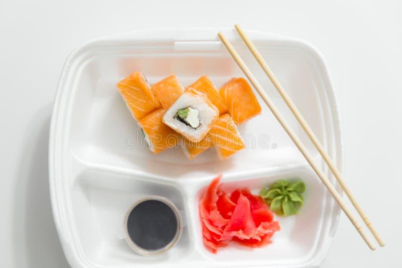 Rotolo con i bastoncini, rotoli, sushi bastoncini, zenzero, salsa di soia nella consegna del contenitore su fondo bianco immagine stock libera da diritti