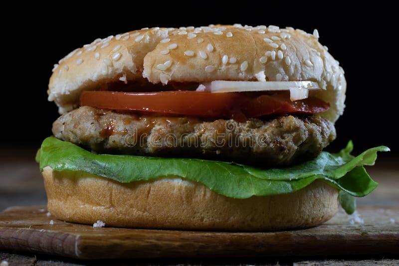 Rotolo con la cotoletta dell'arrosto Hamburger su un bordo di legno Linguetta della cucina fotografia stock