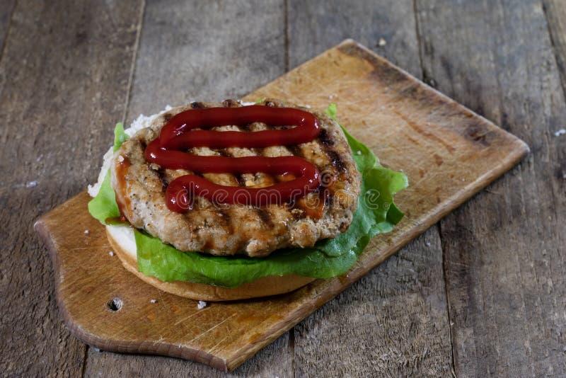 Rotolo con la cotoletta dell'arrosto Hamburger su un bordo di legno Linguetta della cucina fotografia stock libera da diritti