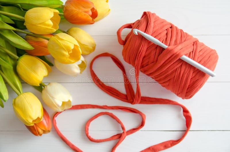 Rotolo del filo di cotone e di un uncinetto con un mazzo dei tulipani arancio e gialli su fondo di legno bianco immagine stock