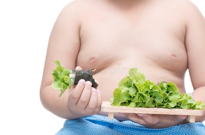 Rotolo dell'insalata sulla mano grassa del ragazzo fotografie stock