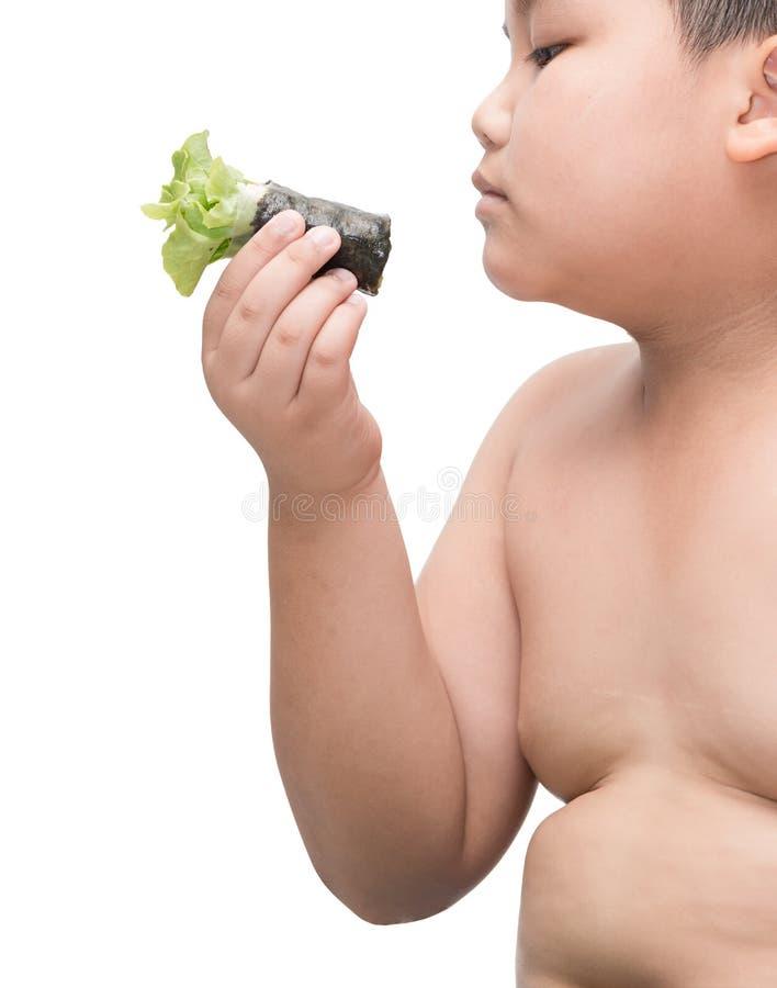 Rotolo dell'insalata sulla mano grassa del ragazzo isolata su fondo bianco fotografia stock