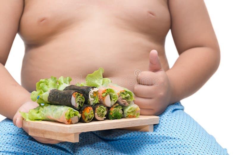 Rotolo dell'insalata sulla mano grassa del ragazzo isolata su fondo bianco immagine stock libera da diritti