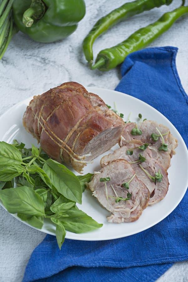 Rotolo della carne di maiale farcito Baked con i verdi servito su un piatto bianco Fondo leggero fotografia stock