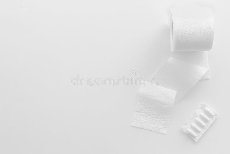Rotolo della carta igienica e supposta rettale per il concetto di malattie di proctologia su derisione bianca di vista superiore  fotografia stock