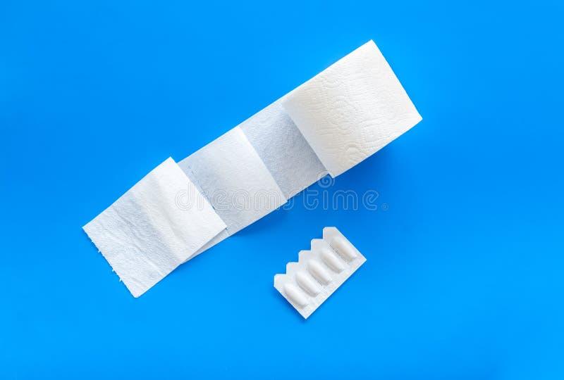 Rotolo della carta igienica e supposta rettale per il concetto di malattie di proctologia sulla vista superiore del fondo blu immagine stock