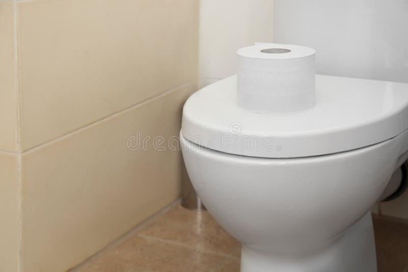 Rotolo della carta igienica sulla copertura della ciotola di toilette in toilette fotografia stock libera da diritti