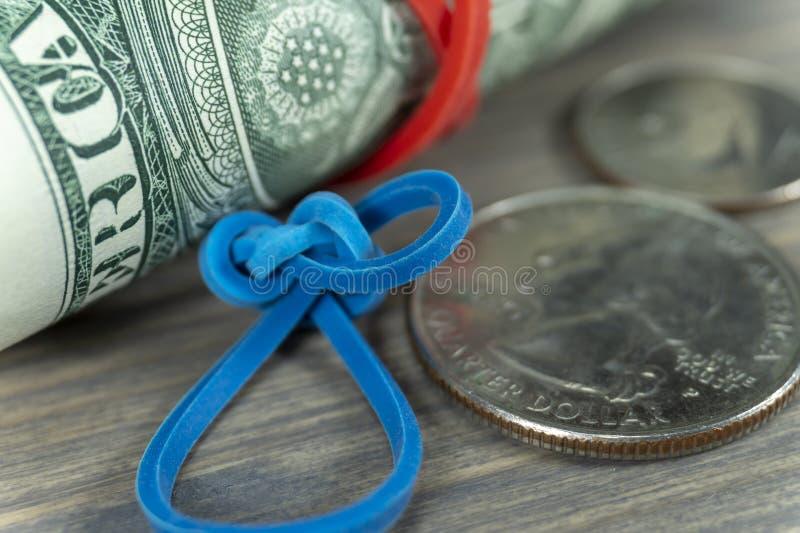 Rotolo delle fatture di USD con l'elastico ed i dollari immagine stock