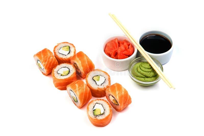Rotolo di Filadelfia, dei sushi con la salsa di soia, wasabi, zenzero e bastoncini su fondo bianco Alimento giapponese fotografia stock libera da diritti
