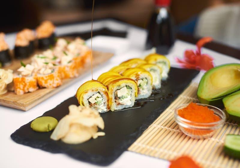 Rotolo di sushi appena preparato coperto dalla salsa di teriyaki fotografia stock