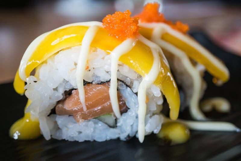 Rotolo di sushi di color salmone con la frutta del mango, stile giapponese dell'alimento su blac fotografie stock