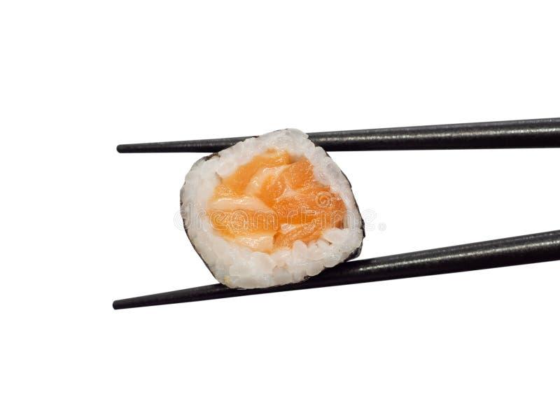 Rotolo di sushi di color salmone giapponese di maki con i bastoncini isolati su bianco fotografia stock