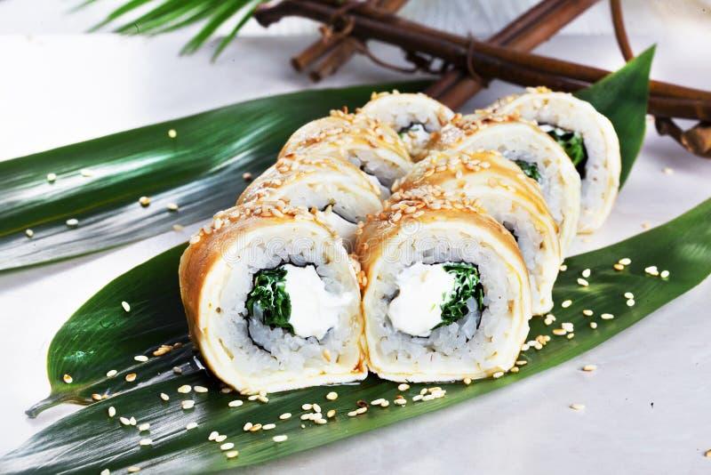 Rotolo di sushi con il formaggio di Filadelfia dell'omelette dell'uovo e le cipolle verdi in cucina tropicale del giapponese dell fotografia stock libera da diritti