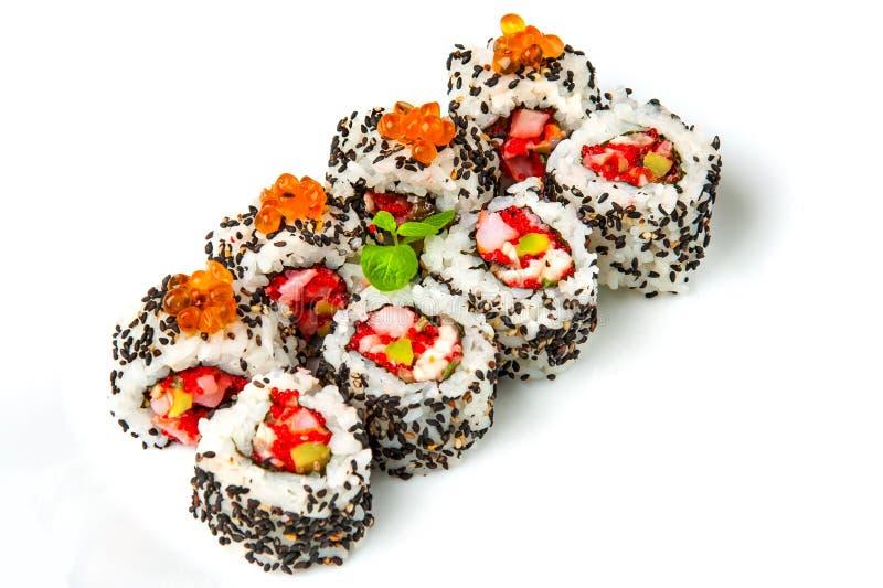 Rotolo di sushi con il sesamo di color salmone e nero del gamberetto, uovo di pesce del pesce volante, immagini stock