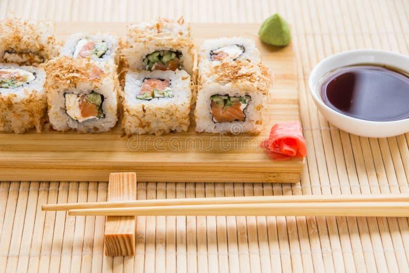 Rotolo di sushi con la pelle del salmone, del cetriolo e del tonno su un bordo di legno fotografia stock libera da diritti