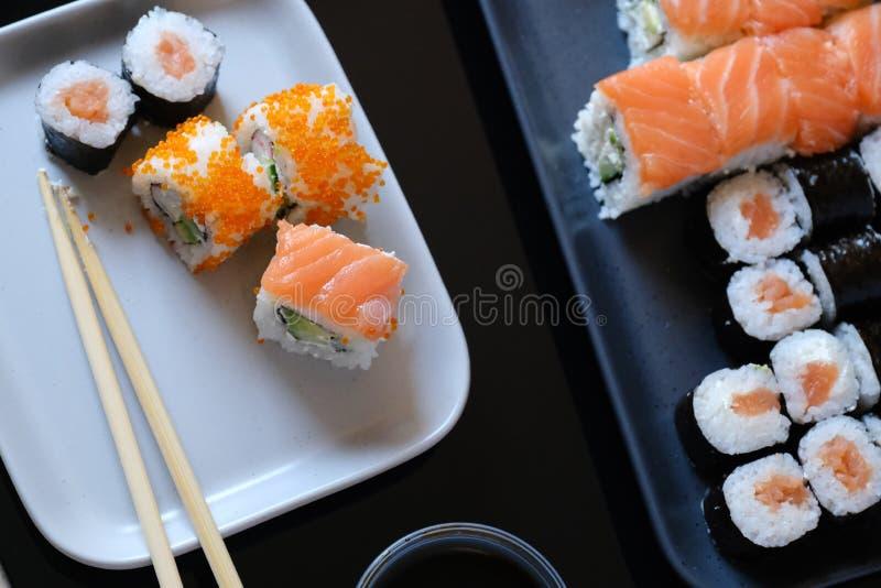 Rotolo di sushi con la salsa di soia e dei frutti di mare, il wasabi e lo zenzero Rotolo di sushi con il caviale del pesce volant immagini stock libere da diritti