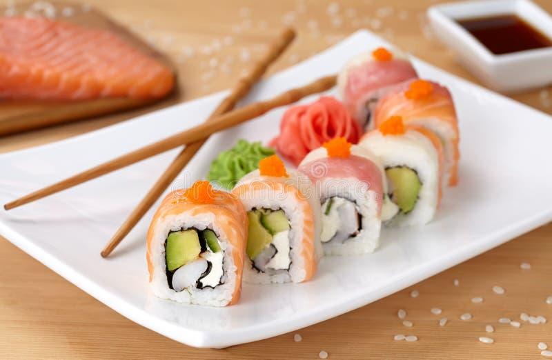Rotolo di sushi del drago dell'arcobaleno con il salmone, avocado fotografia stock libera da diritti