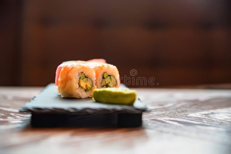 Rotolo di sushi dell'arcobaleno con wasabi sulla fine del vassoio su immagini stock