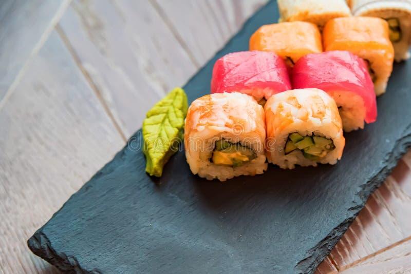 Rotolo di sushi dell'arcobaleno con wasabi sulla fine del vassoio su immagine stock libera da diritti