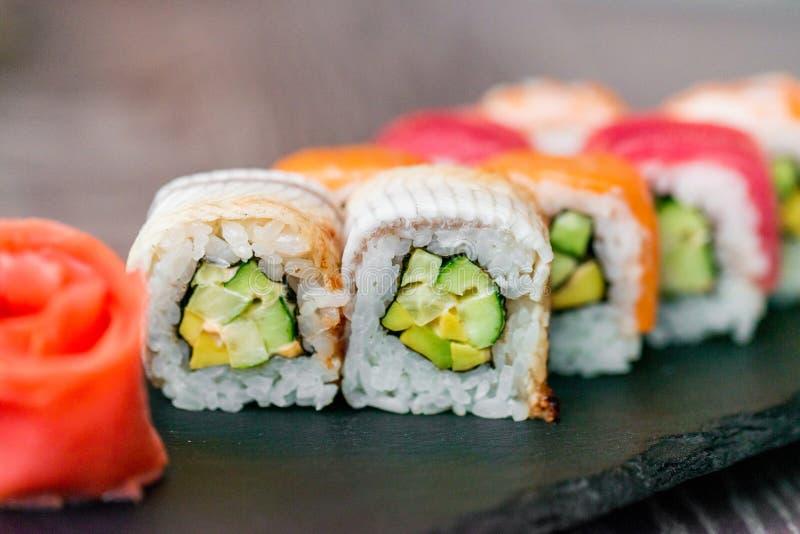 Rotolo di sushi dell'arcobaleno sul vassoio con la fine dello zenzero su immagine stock