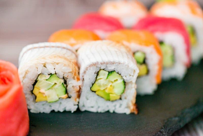 Rotolo di sushi dell'arcobaleno sul vassoio con la fine dello zenzero su fotografia stock libera da diritti