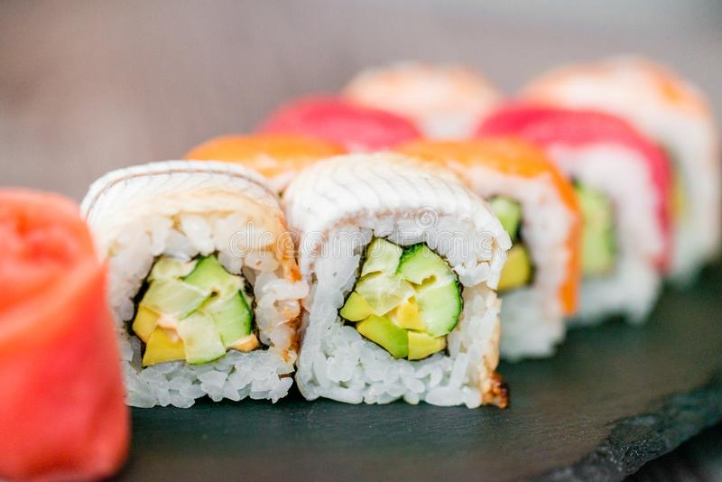 Rotolo di sushi dell'arcobaleno sul vassoio con la fine dello zenzero su immagini stock