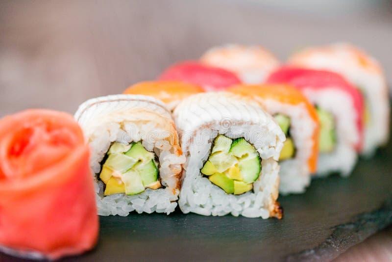 Rotolo di sushi dell'arcobaleno sul vassoio con la fine dello zenzero su fotografie stock