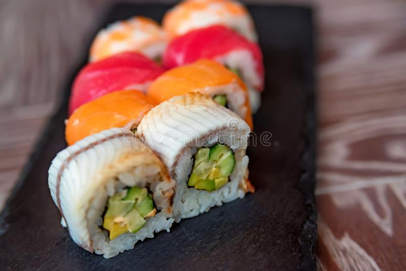 Rotolo di sushi dell'arcobaleno sulla fine del vassoio su immagini stock libere da diritti