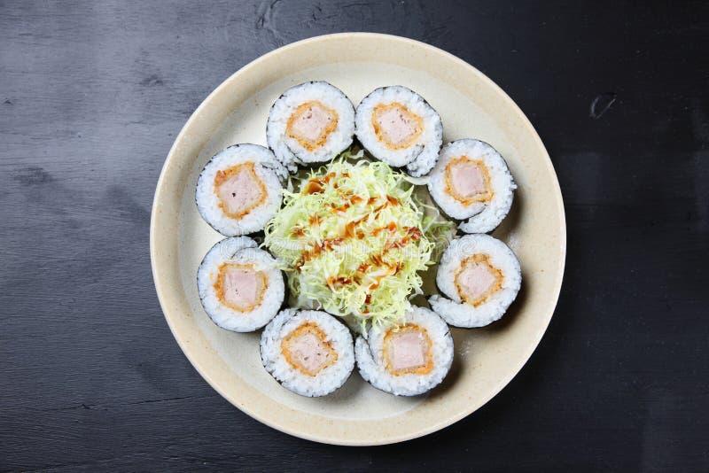 Rotolo di sushi della cotoletta della carne di maiale su un tavolo da pranzo fotografia stock libera da diritti