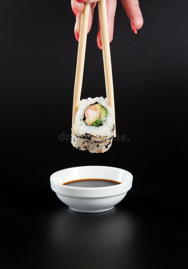 Rotolo di sushi della tenuta, rotolo di sushi sulla salsa di soia, alimento giapponese immagine stock libera da diritti