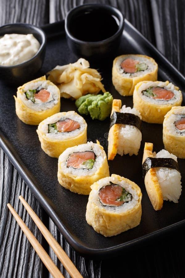Rotolo di sushi giapponese di tamagoyaki dell'insieme della prima colazione con il primo piano del riso, del formaggio, del salmo immagine stock